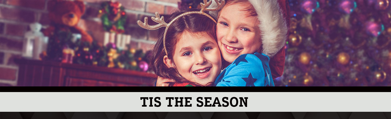 "Kids hugging at with holiday decoration and tagline ""tis the season"" below"