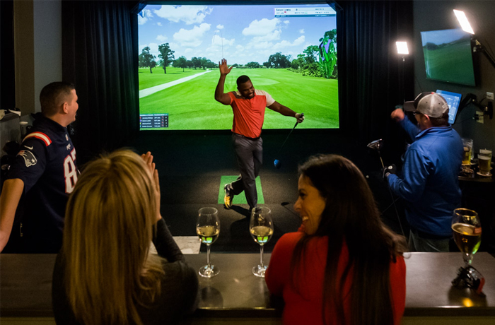 Friends celebrating a great virtual shot at North Swing Golf lounge Barrie