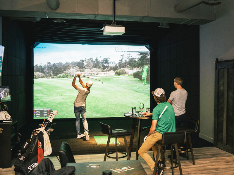 people playing golf in a indoor simulator